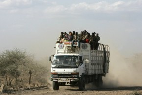 A truck carrying people drives through a dusty road near Isiolo town